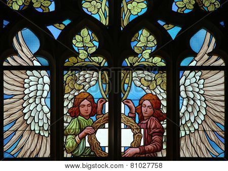 Angels holding the True Cross and the Crown of Thorns. Art Nouveau stained glass window in Saint Barbara Church in Kutna Hora, Czech Republic.