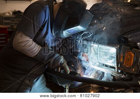Man welding the bumper of a vehicle