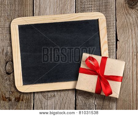 Blank Blackboard And Gift Box On Wooden Background