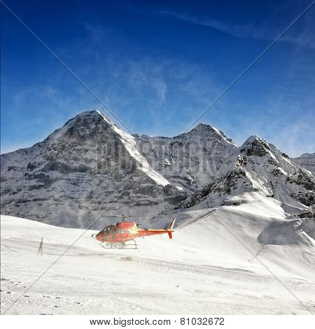 Red Helicopter Raising Snow Powder At Take-off From Alpine Resort