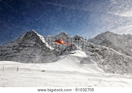 Red Helicopter Taking-off With Snow Powder Clouds From Alpine Resort
