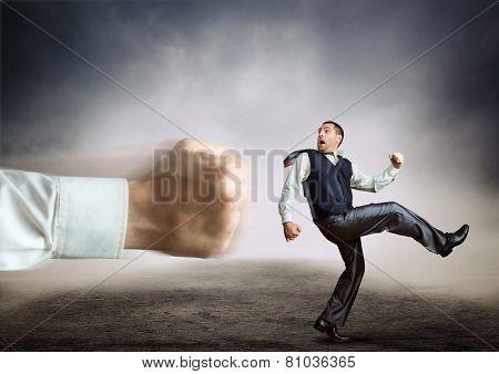 Businessman runs from a big fist