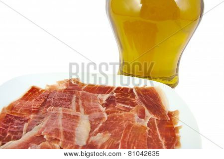 Spanish serrano ham with olive oil on white background.