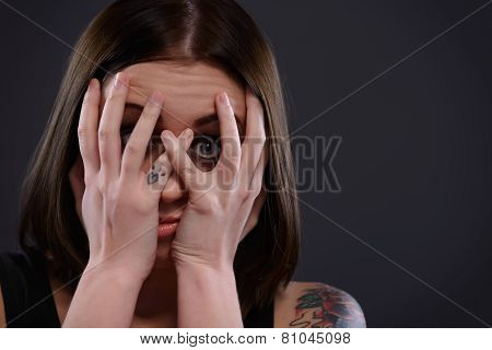 Teenage girl frightened looking through fingers