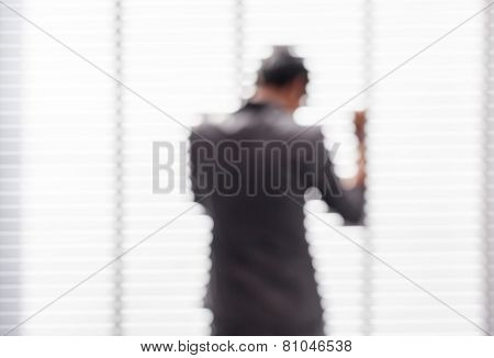 Blurred Picture Of Young Business Man Stands Near The Window With The Action Of Success.