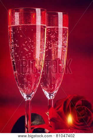 Valentine day dinner, two elegant glass of champagne decorated with red rose and candle, romantic still life, love and passion concept