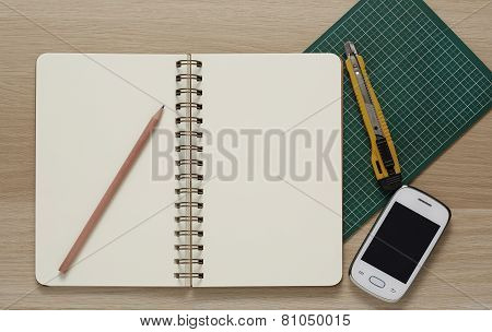 Blank Spiral Note Pad, Cutter, Cellphone And Pencil On Wood Background.