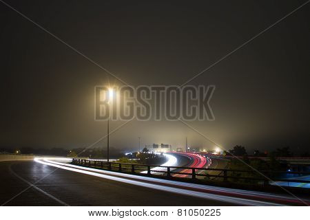 Highway on a foggy night with car light trails