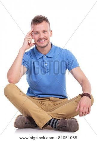 casual young man sitting on the floor with his legs crossed and smiling for the camera while holding a hand at his head in a pensive manner. isolated on white