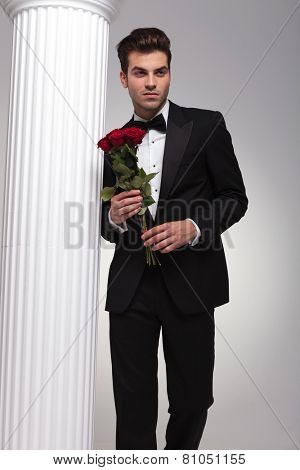 Handsome young business man posing near a white column with a bouquet of red roses in his hand, looking away from the camera.