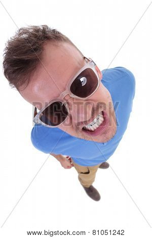 top view of a casual young man showing his teeth to the camera with an angry expression. on a white background