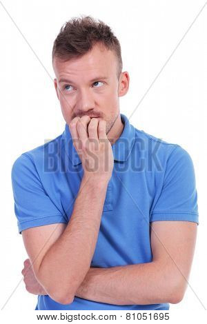 portrait of a young casual man thinking while biting his nails and looking away. isolated on a white background