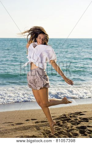 Young Female Jumping At The Beachfront