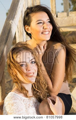 Pretty Female Friends Sitting On Wooden Stairs