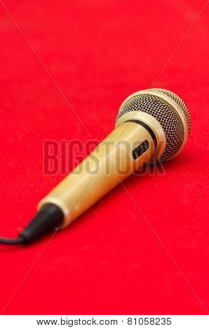 Golden Microphone On Red Background.