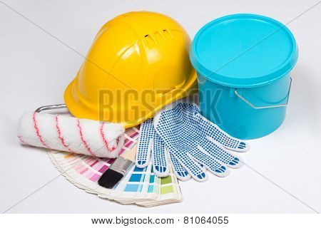 Painter's Tools - Brushes, Work Gloves, Helmet And Bucket Of Paint Over White