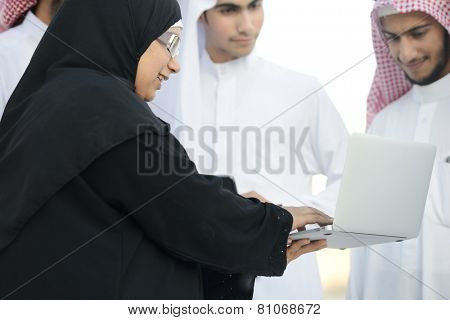Young Arabic Muslim business woman leading group of Middle eastern Gulf guys