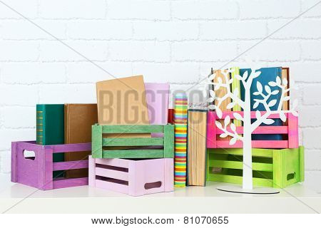 Many books in crates on brick wall background