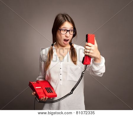 young girl holding a telephone on gray background