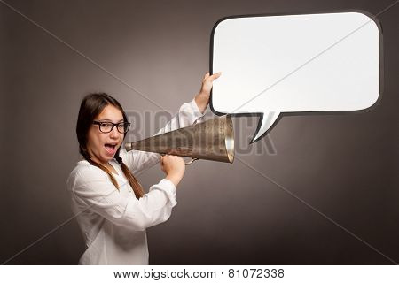 young girl shouting with an old megaphone on a gray background