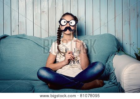 Little girl making faces with mustache props