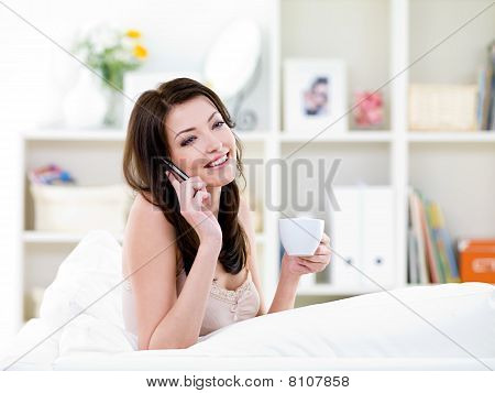 Woman With Cup Speaking By Mobile Phone