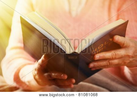 Old woman reading Bible, closeup