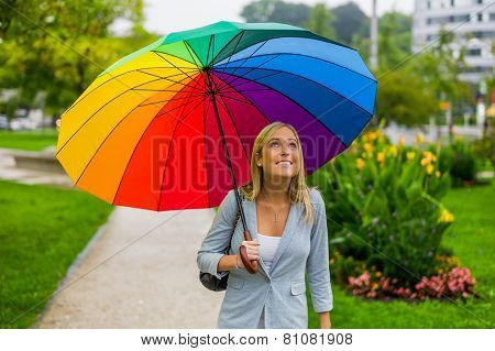 a young woman walks with a colorful umbrella in hand walking in the rain