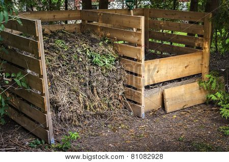 Wooden compost boxes with composted soil and yard waste for garden composting in backyard