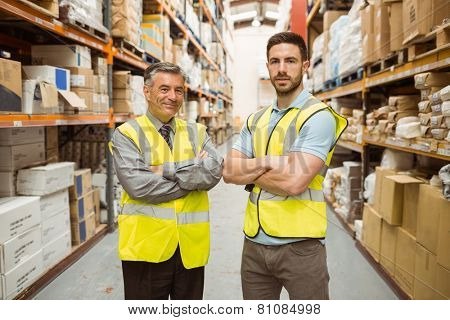 Warehouse team standing with arms crossed in a large warehouse