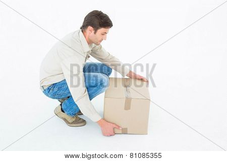 Delivery man crouching while picking cardboard box against white background