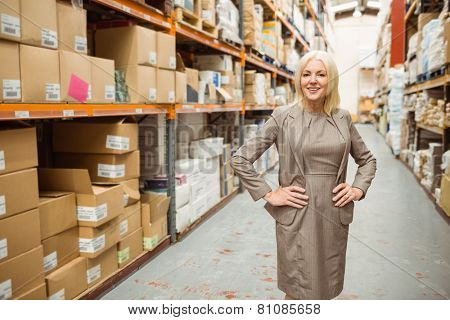 Smiling manager placing her hands on her hips in a large warehouse