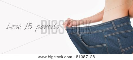 Close up of a woman belly in too big pants against white background