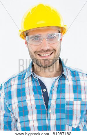 Portrait of confident repairman wearing protective glasses on white background