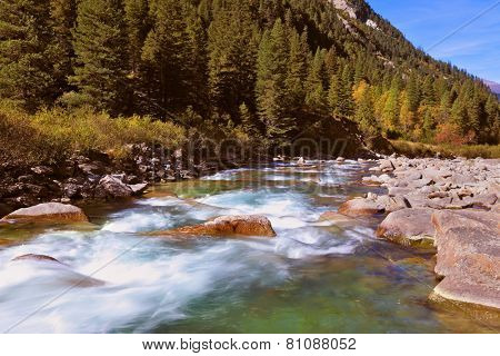 Pastoral in the Alpine mountain valley in Austria. Rapid mountain stream. Cascades of cold water at the source of the famous Krimml waterfalls