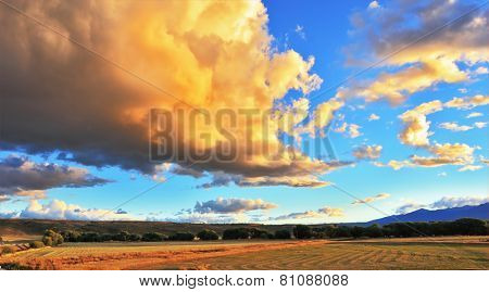Improbably beautiful huge storm the cloud is shined with the sunset. The cloud hangs over the gravel road