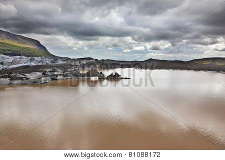 Skaftafell National Park.  Ice covered with volcanic ash. Mirror Lake, formed as a result of thawing of a glacier Vatnajokull glacier spurs. Iceland in July