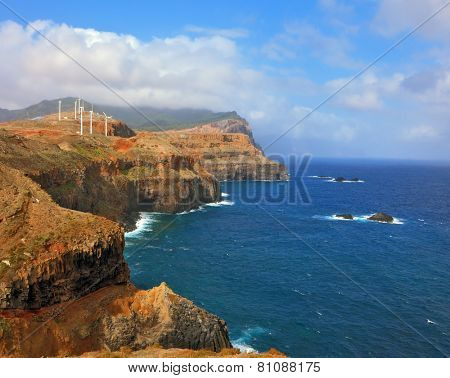 Over a cliff on the ocean breeze are the windmills. Eastern tip of the island of Madeira. Rocks steeply in the blue waters of the Atlantic Ocean.