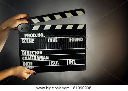 Movie clapper in female hand on dark color background