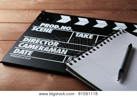 Movie clapper with notebook and pen on wooden background