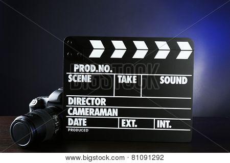 Photo camera and movie clapper on dark background
