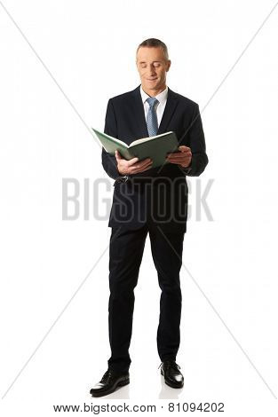Mature businessman reading his note book.