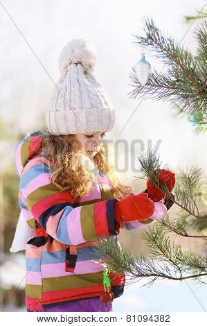 Child Decorates A Christmas Tree Outdoors