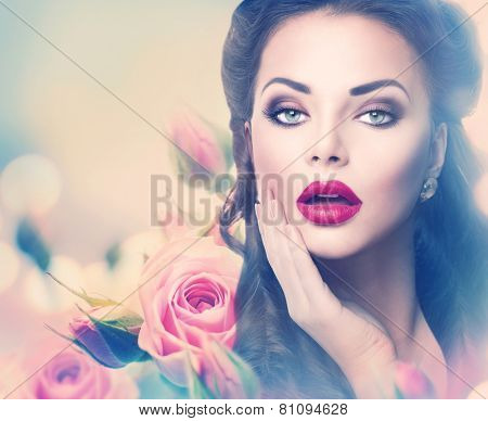Retro woman portrait in beauty pink roses. Beautiful Vintage styled girl with flowers. Perfect makeup and hairstyle. Gorgeous model lady. Red Lips. Luxury Make up and Hair. Vogue Style