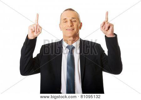 Portrait of businessman pointing upwards.