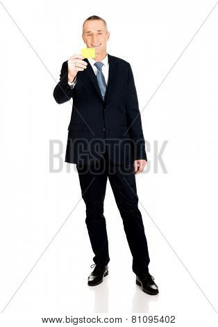 Full length businessman showing a yellow card.