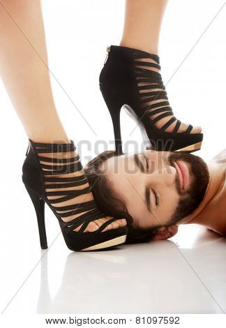 Sexy woman's foot in high heel on man's face, dominating him.