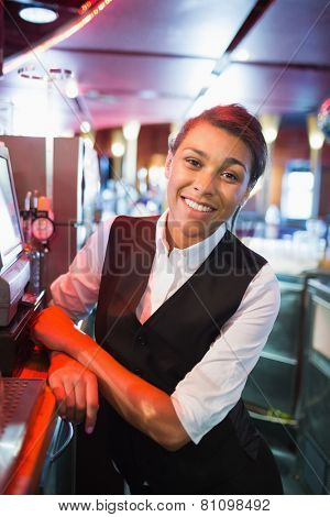 Pretty barmaid smiling at camera in a bar