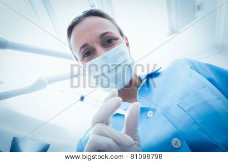 Low angle portrait of female dentist in surgical mask holding injection