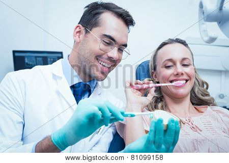 Male dentist teaching woman how to brush teeth in the dentists chair